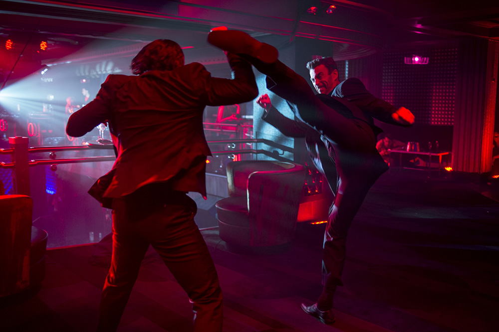 Daniel Bernhardt as Kirill with a high kick in his fight scene against Keanu Reeves as John Wick in the Red Circle Club