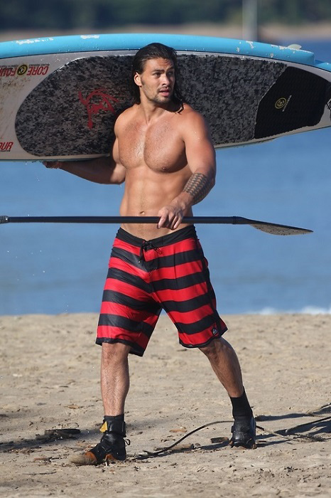 Jason Momoa with surfboard and paddle