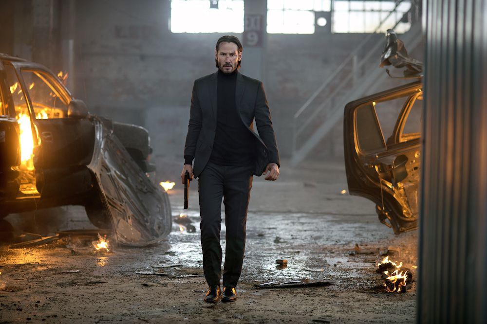 Keanu Reeves struts through bits of burning cars on the ground with locomotive breath in the scene where he kills Iosef