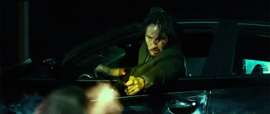 Keanu Reeves as John Wick makes a headshot out the window of his Dodge Charger