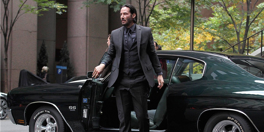 Keanu Reeves as John Wick steps out of his Chevy Chevelle SS to check into The Continental Hotel in John Wick