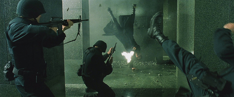 Keanu Reeves as Neo in The Matrix shoots while doing a cartwheel