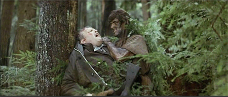 camouflaged with ferns and mud, a Rambo trademark, Rambo has a knife to Sheriff Teasle's throat in the forest in First Blood