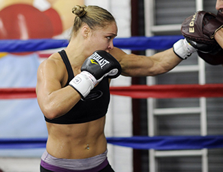 Ronda Rousey showing strong arms with boxing gloves