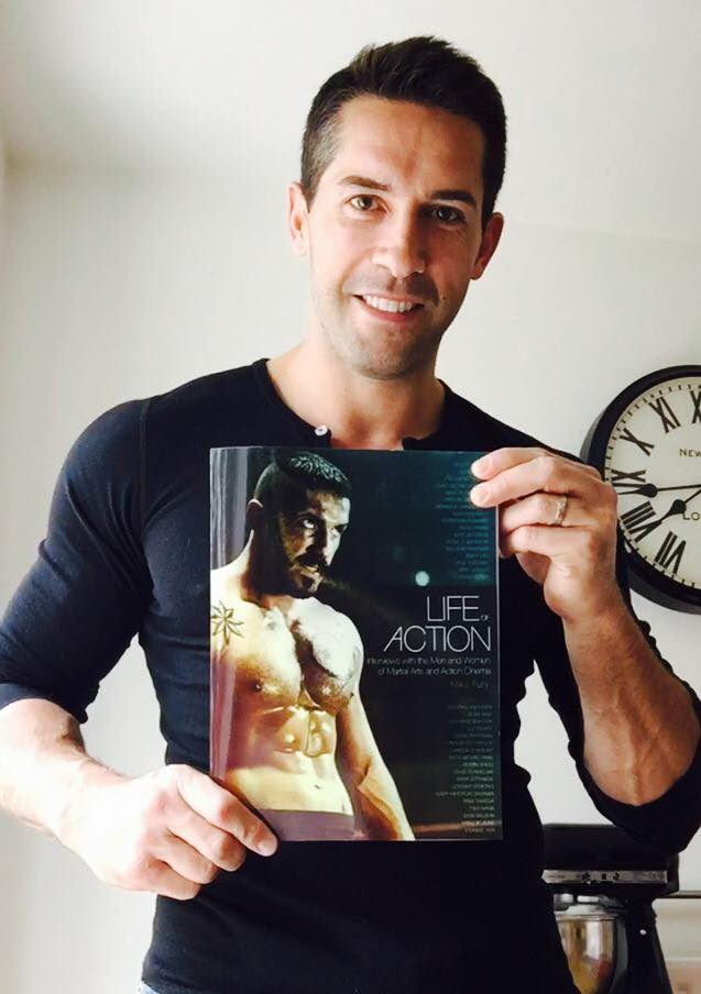 Scott Adkins holding the book Life of Action by Mike Fury