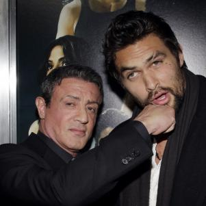 Sylvester Stallone pretend punches Jason Mamoa for a promotional shot for Bullet to the Head