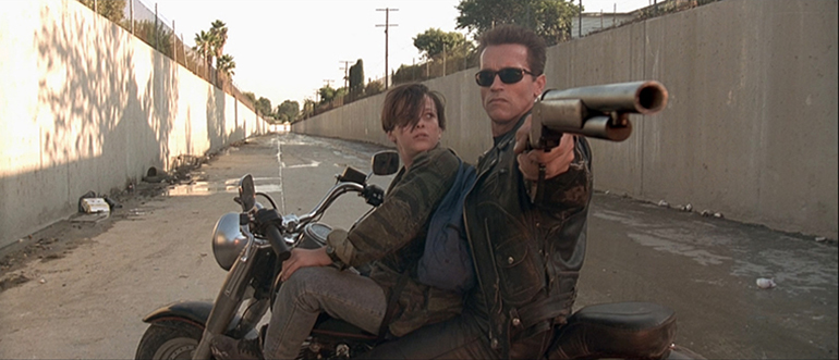 Arnold as the terminator in Terminator 2: Judgment Day aims his shotgun back at the crashed semi driven by the T1000