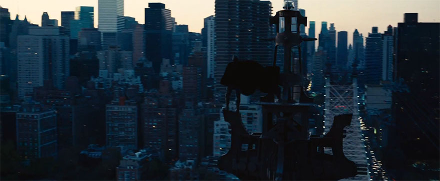 The Dark Knight Rises Batman standing on skyscraper tower with cape blowing in the wind