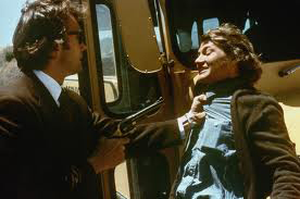 Clint Eastwood as Inspector Callahan points gun at serial killer in front of school bus in Dirty Harry