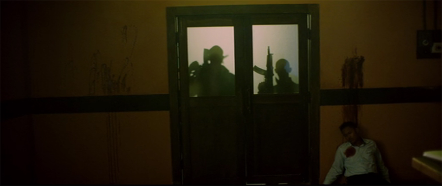 silhouette of two men waiting with big guns seen through double doors with frosted windows on the top half from Headshot movie