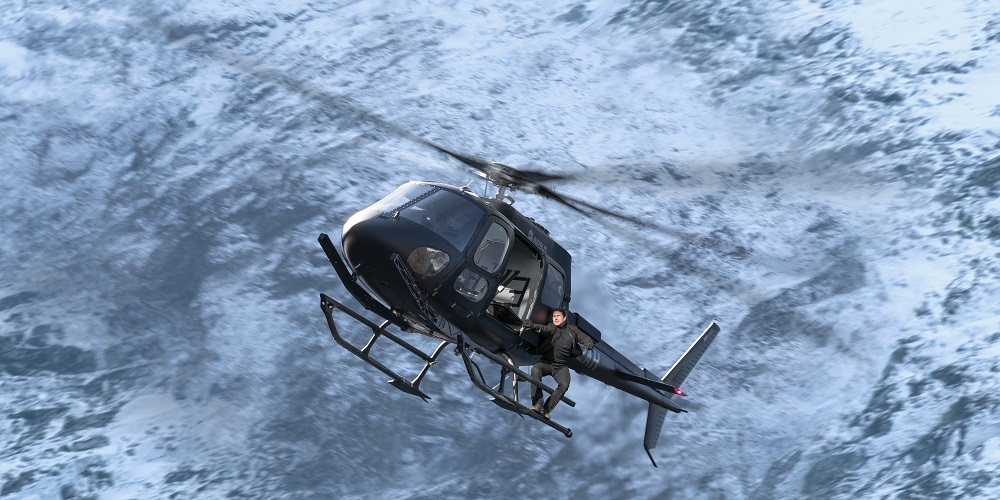 Tom Cruise stands on the outside of a moving helicopter in Mission: Impossible - Fallout