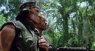 Predator movie Billy and Dutch stare into the jungle seeing nothing as Billy the Indian Tracker rubs his medicine pouch