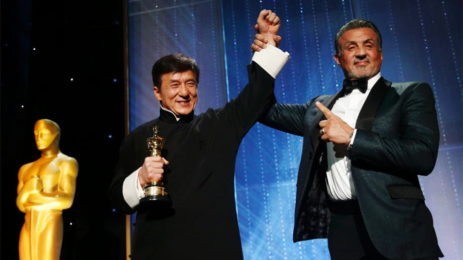Sylvester Stallone points at Jackie Chan holding his Oscar, as Stallone raises Jackie's arm like a champ