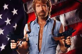 Chuck Norris with guns in both hands in front of an American flag