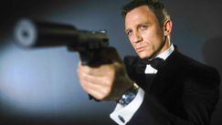 Daniel Craig as James Bond aiming a gun with a silencer