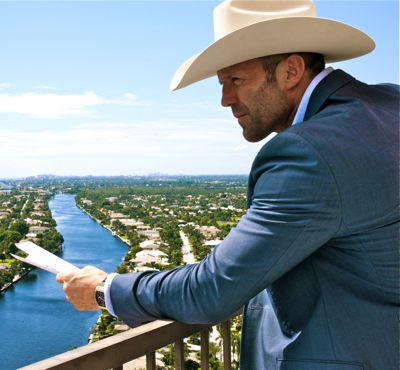 Jason Statham as Parker in a blue suit and white Stetson on the balcony