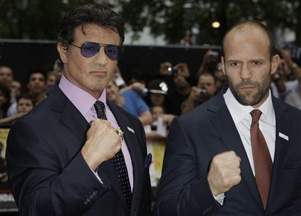 Sylvester Stallone and Jason Statham on the red carpet in suits and ties and making fists