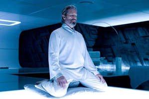 Jeff Bridges kneels on a matt in a yoga pose from Tron Legacy